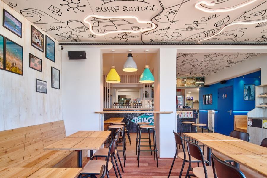 """Carré Chroma - Le surf des années 50... - ANGLET Rénovation du restaurant """"Le Bilagoon"""". Les codes de cette époque. Une série de photos. Le choix du bois et du bleu. Un concept éclairage au look coloré et rétro. Le plafond et son traitement stickers avec des pictogrammes."""